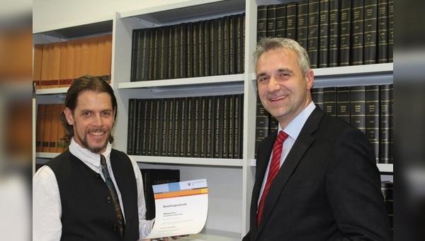 Dr. Tobias Mehlich, Hauptgeschäftsführer der Handwerkskammer Ulm, gratuliert Matthew J.G. Price nach seiner Vereidigung.
