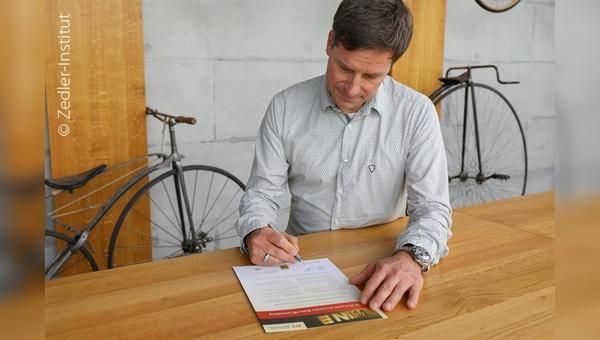 Dirk Zedler unterschreibt die WIN-Charta Urkunde.